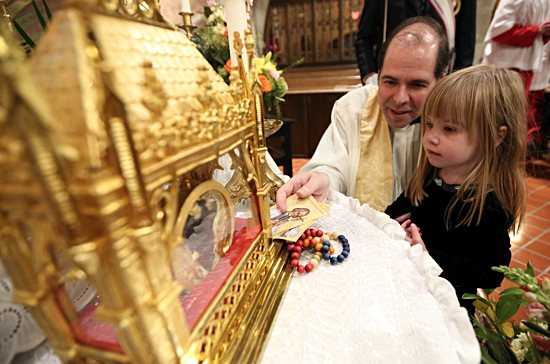 Maria O'Brien of Holy Family in St. Louis Park approaches a reliquary containing the heart of St. John Vianney May 30 with guidance from Father Joseph Johnson, pastor of Holy Family, during an event at the church to honor the saint and venerate his incorrupt heart.