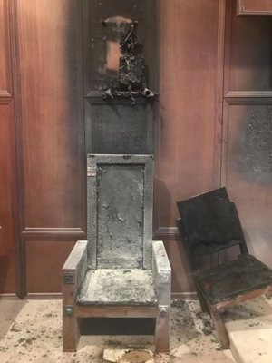 The charred remains of the cathedra, or bishop's chair, and the presider's chair in the sanctuary of the Co-Cathedral of St. Thomas More in Tallahassee, Fla