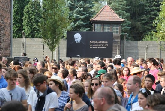 World Youth Day pilgrims and other visitors pause near an image of St. Maximilian Kolbe during a visit to the Auschwitz Nazi concentration camp in Oswiecim, Poland.