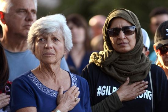 Women attend a candlelight vigil outside Gilroy City Hall in California July 29, 2019, during the singing of the National Anthem honoring those who died and were injured during a mass shooting at the Gilroy Garlic Festival. The Diocese of San Jose held a bilingual prayer vigil July 29 for victims, survivors and first responders at St. Mary Church in Gilroy in response to the the shooting a day earlier that claimed three lives and injured 12 others.