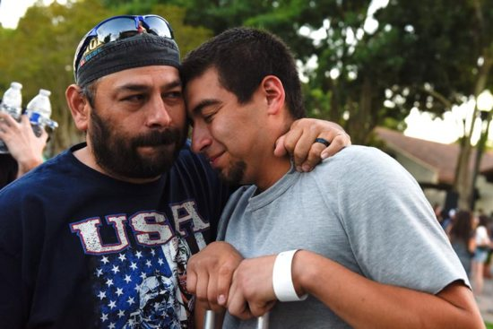 Justin Bates, right, a survivor of the Gilroy Garlic Festival mass shooting, is comforted by his father, Rob Bates, during a candlelight vigil outside Gilroy City Hall in California July 29, 2019. The event honored those that died and were injured during the shooting a day earlier. The Diocese of San Jose held a bilingual prayer vigil July 29 for victims, survivors and first responders at St. Mary Church in Gilroy in response to the shooting that claimed three lives and injured 12 others.