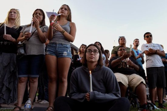 People attend a candlelight vigil outside Gilroy City Hall in California July 29, 2019, honoring those that died and were injured during a mass shooting at the Gilroy Garlic Festival a day earlier. The Diocese of San Jose held a bilingual prayer vigil July 29 for victims, survivors and first responders at St. Mary Church in Gilroy in response to the the shooting that claimed three lives and injured 12 others.