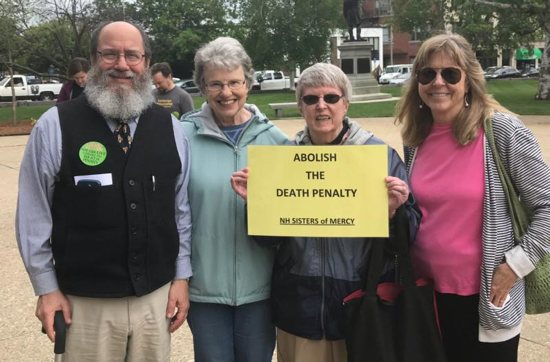 Mercy Sister Mary Ellen Foley holds a sign while standing other members of the New Hampshire Coalition to Abolish the Death Penalty