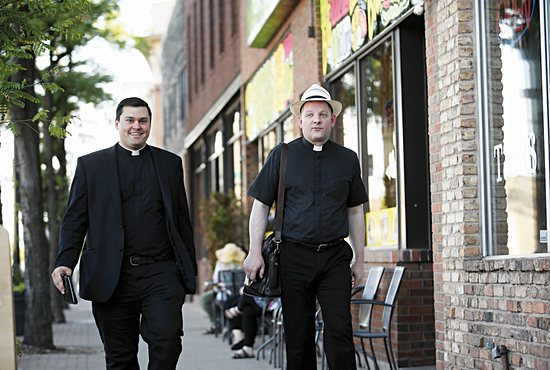 Fathers Spencer Howe and Byron Hagan walk down Central Avenue in Northeast Minneapolis