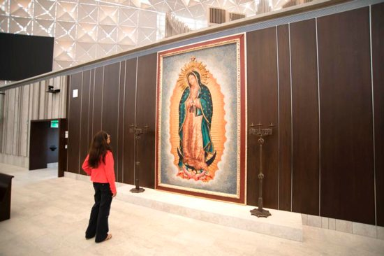 A woman looks at a large tile mosaic of Our Lady of Guadalupe June 21, 2019, in the Christ Cathedral