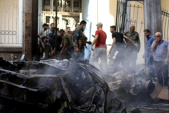 People gather at the site of a car bomb blast outside the Syriac Orthodox Church of the Blessed Virgin Mary in Qamishli, Syria