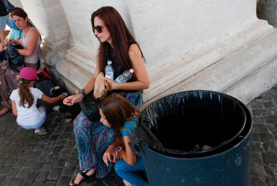 A woman holds water bottles next to a trash can under the St. Peter's Square colonnade at the Vatican