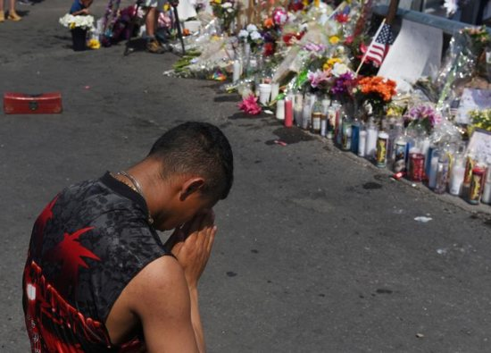 A man prays at a memorial