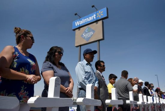People stand near crosses Aug. 5, 2019, in honor of the victims of a mass shooting Aug. 3 at a Walmart store in El Paso, Texas.