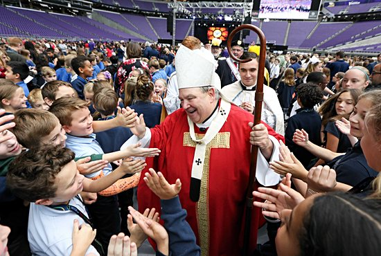 Archbishop Hebda warmly greets elementary school students at a school-focused Mass of the Holy Spirit at U.S. Bank Stadium