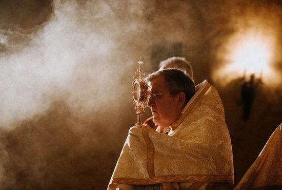 Cardinal Raymond Burke holds the monstrance during Mass