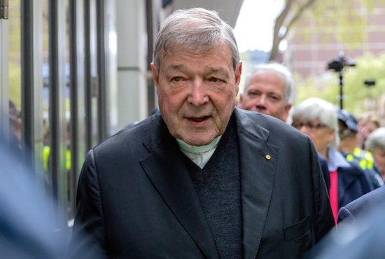 Australian Cardinal George Pell is surrounded by police as he leaves the Melbourne Magistrates Court in Australia