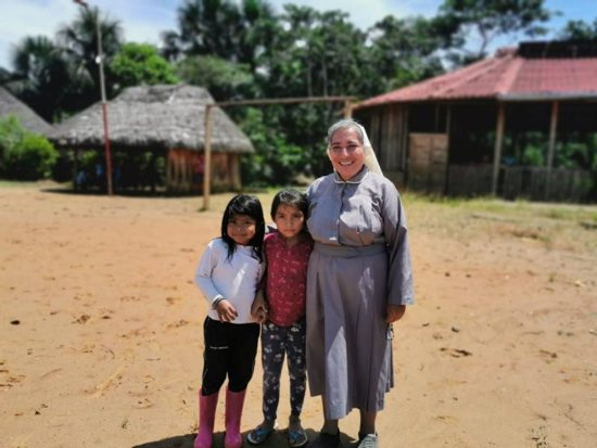 Sister Rosa Elena Pico, a member of the Missionaries of Mary Co-Redemptrix, poses for a photo with children from the indigenous community of Sarayaku, Ecuador, Sept. 18, 2019. Sr. Pico has worked and lived with the community since 2017 and occasionally leads the liturgy of the word in the absence of a priest.