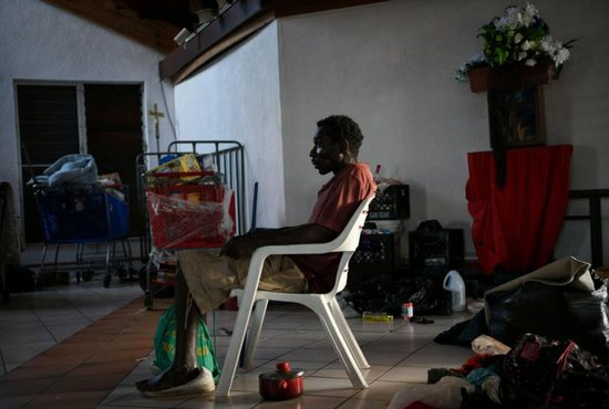 A man sits inside a damaged church serving as a shelter in Marsh Harbour, Bahamas