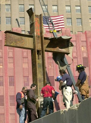 Franciscan Father Brian Jordan, standing with laborers and emergency workers in Oct. 5, 2001, blesses a 17-foot-tall cross formed by steel beams that was recovered from the rubble of the World Trade Center
