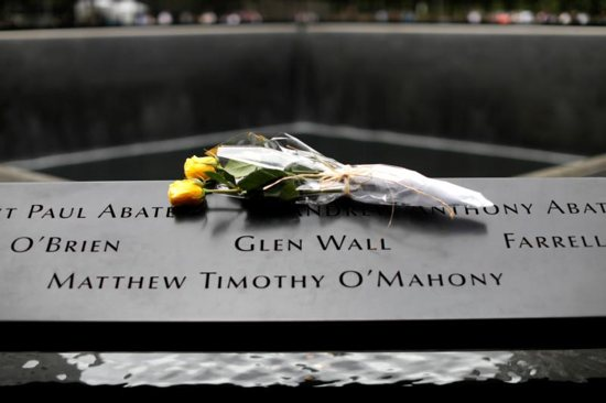 Flowers are seen left at the edge of the north reflecting pool at the 9/11 Memorial and Museum in New York City