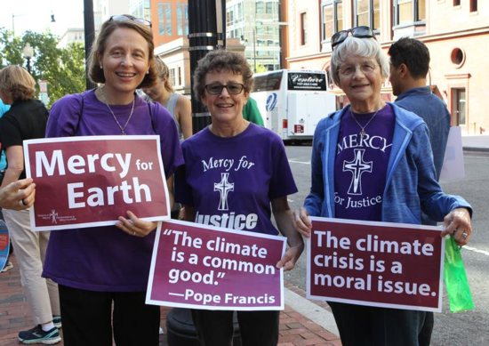 Mercy Sister Aine O'Connor, Marianne Comfort, justice coordinator for the Mercy Sisters, and Mercy Sister Rita Parks, all from Silver Spring, Md., hold aloft signs