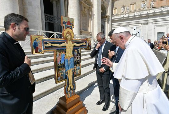 Pope Francis blesses a cross during an audience with members of the Italian Prison Police