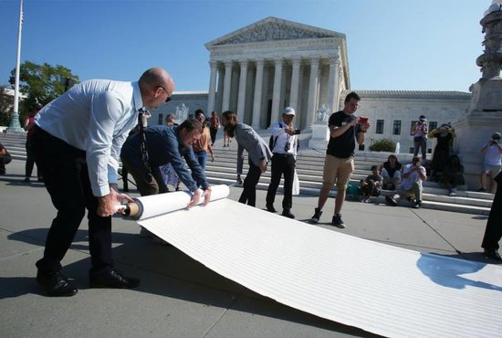 Pro-life leaders unfurl a petition in front of the U.S. Supreme Court