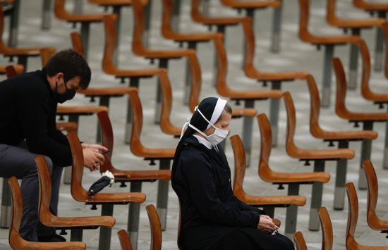 People wear masks for protection from COVID-19 as Pope Francis leads his general audience in Paul VI hall at the Vatican Oct. 14, 2020. A few days after four Swiss Guards tested positive for COVID-19, the pope broke from his normal pattern and did not personally greet people in the crowd.