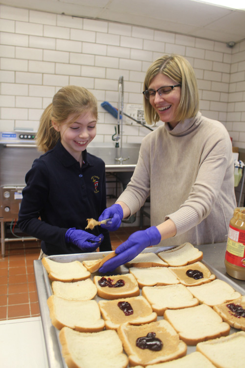 Students at Holy Cross School in DeWitt helped to make more than 240 sandwiches for the Samaritan Center in Syracuse, an interfaith organization that feeds those in need. Here, third grader Layla McIntyre and her mother Jennifer McIntyre make peanut butter and jelly sandwiches.