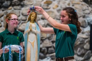 Sixth graders, Mary Lousie Pemfield, left and Nikki Limer,12,  from All Saints School Thursday crowned the Blessed Mother at the Marian Shrine at St. Joseph Church in Endicott. Their essays  about the Blessed Mother were picked for the honor of placing the crown of flowers. -Sun photos | Chuck Haupt