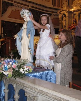 Marlena Venette, with teacher's aide Samantha Staley, crowns the Blessed Mother at St. Joseph and St. Patrick Church in Utica May 8. (Sun photo | Tom Loughlin, Jr.)