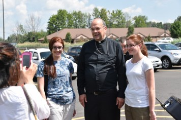 Bishop Cunningham stops for a photo with two of the pilgrims. (Sun photo | Katherine Long)