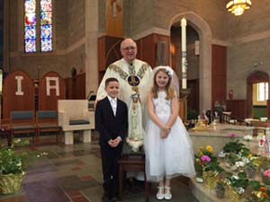 Blessed Sacrament School's second-grade First Communicants crowned the Blessed Mother May 12 at a morning liturgy. Pictured with Father Peter Reddick are Joseph Wesley Calangelo Amiah Emig. -Photo courtesy Blessed Sacrament School