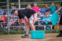 Seminarian Nathan Brooks launches a water balloon to kids in the outfield in-between innings during the Men In Black softball game in Endicott on Sunday.