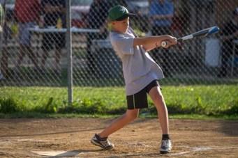 OLGC parishoner Noah Pangilinan swings while at bat during the Men In Black softball game in Endicott on Sunday.