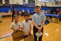 Kindergartners Gianni Bruno, left, and Paul Mullin are set for some shopping with their sixth-grade buddy, Ryan Hayden.