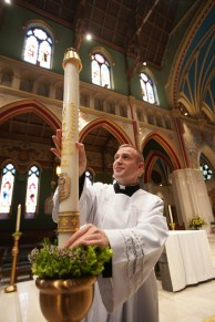 Seminarian Brendan Foley sets up candles, specially designed by Syracuse's Cathedral Candle Company, commemorating Bishop Cunningham's 50th ordination anniversary. (Sun photo | Chuck Wainwright)