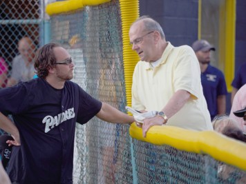 Father Chris Celentano and Bishop Robert J. Cunningham chat during the game. (Sun photo | Chuck Wainwright)