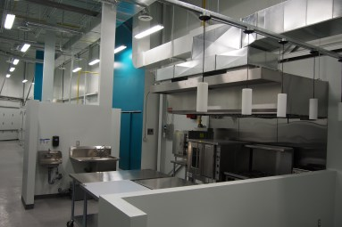 commercial kitchen with hood vent, hand washing sinks, food sink, stainless steel tables.