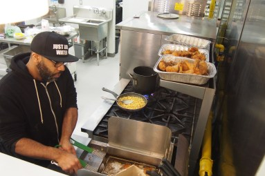 Chef LeRoy frying up chicken and making Mac n Cheese.