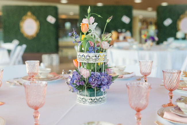 Bridal shower theme: Afternoon tea. Tables decorated in pastels with a beautiful floral arrangement on a small cookie holder as the centerpiece