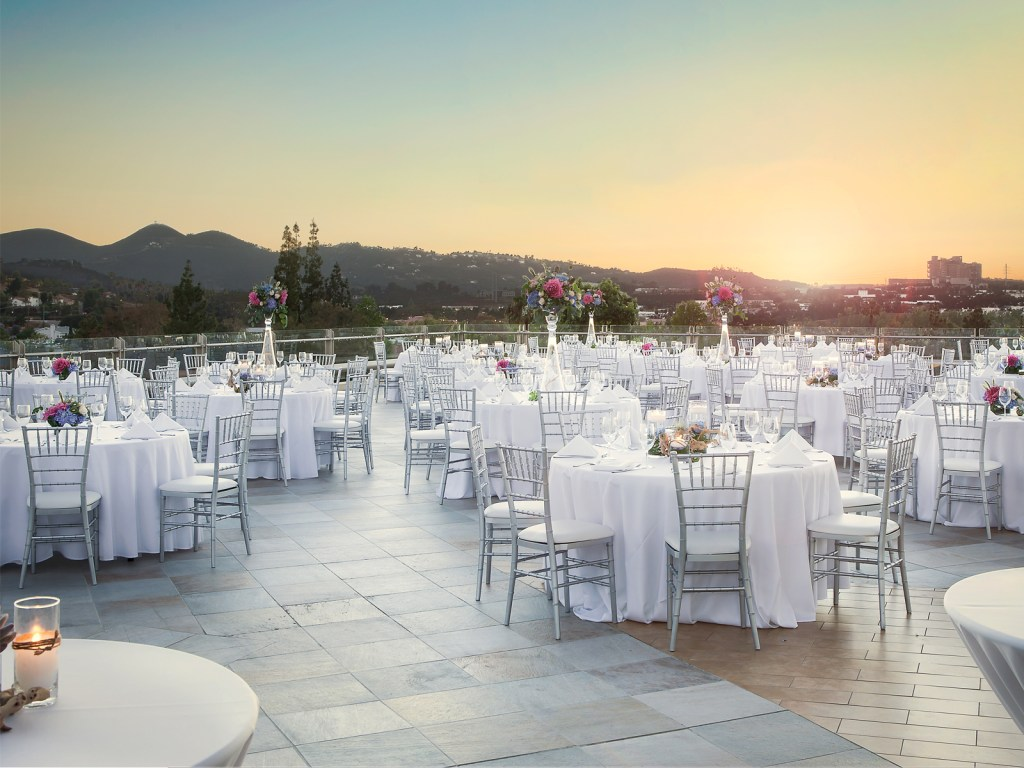A wedding reception venue surrounded by North County San Diego mountains. It has over 10 round tables showing with white tablecloths and purple and pink bouquets at various sizes.