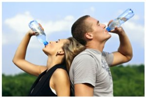 athletic-woman-and-man-drinking-bottled-water
