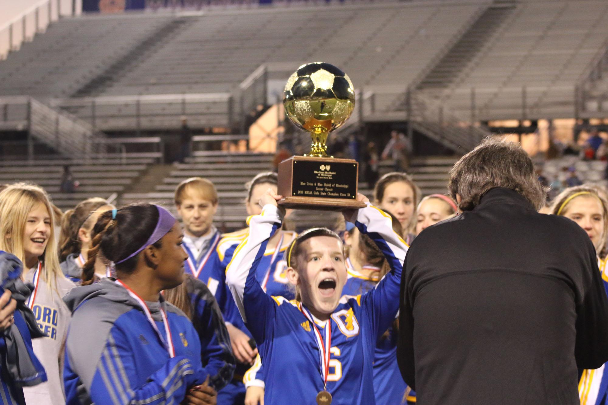 (PHOTOS BY SARIYA KHAN)  OHS senior girls soccer player Sarah Nash hoists the MHSAA Class 5A state soccer championship trophy following the Lady Chargers win against West Harrison High.