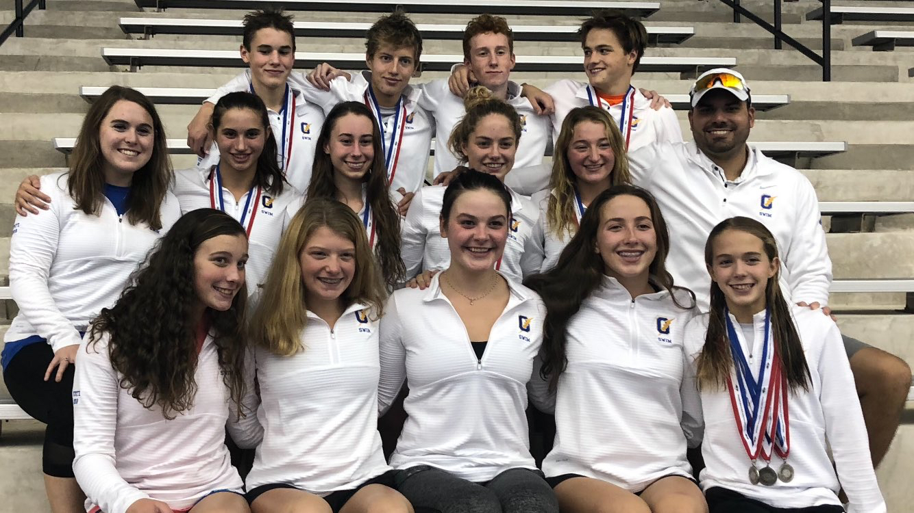 Members of the swim team smile with their head coach Robert Gonzales after their state meet. Overall, the team placed third at the meet on Oct. 27.