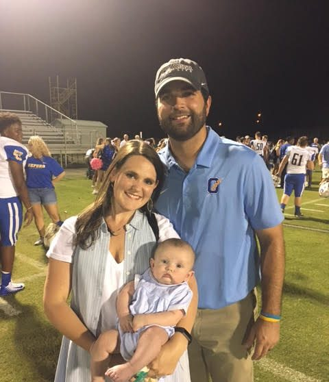 Logan Dodson poses with his wife, Kelsey, and son, William 'Still' after a football game. Dodson recently got married and had a child.