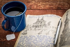 travel journal on desk with tea