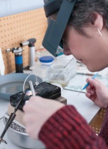 Photo of E Pelati Soldering work at her bench for museum stores and galleries.