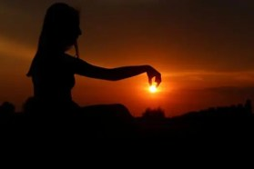 Woman meditation in profile against setting sun, appearing to hold the sun in her fingertips
