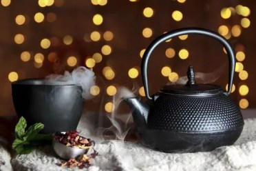 black cast iron little japanese tea pot with steaming cup of tea set in front of fairy lights. pexels-photo-327136