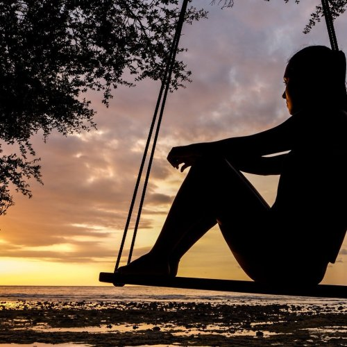 artist daydreaming on a swing at sunset