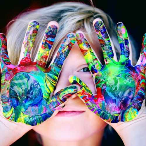 Little artist with spectrum of paint colors on her open palms