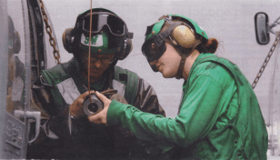Photo depicting AM2 LINDSAY ZIKE (right), and AM3 JAMES BRINKLEY (left)  lubricate rescue hoist of SH-60F Seahawk on flight deck of the aircraft carrier USS Kitty Hawk, 2007. Used with permission of artist and veteran Linsday Like.