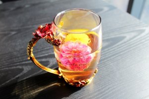 photo of rose infused tea in a glass cup. Tea helps artists remember what is important to them.